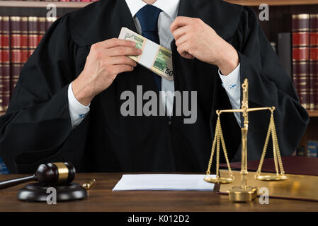 Midsection of corrupt judge putting dollar bundle in pocket at courtroom - Stock Photo