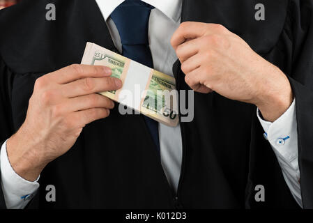 Closeup midsection of corrupt judge putting dollar bundle in pocket - Stock Photo