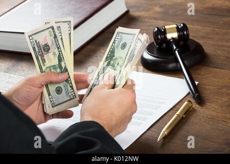 High angle view of corrupt judge counting money at desk in courtroom - Stock Photo