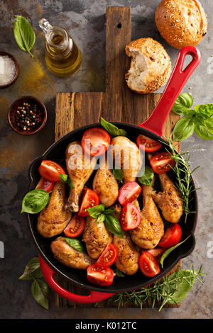 Roasted chicken drumsticks in a cast iron pan - Stock Photo