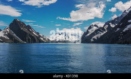 Dramatic scenery of glacial Drygalski Fjord on South Georgia Islands. Steep snow capped mountains beside deep bay. - Stock Photo