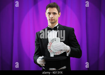 Portrait of young magician putting playing cards in hat against purple curtain - Stock Photo