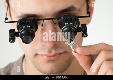 Closeup of jeweler examining diamond ring with magnifying loupe against white background - Stock Photo