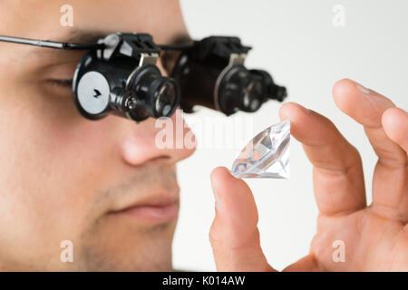 Closeup of jeweler examining diamond with magnifying glass against white background - Stock Photo