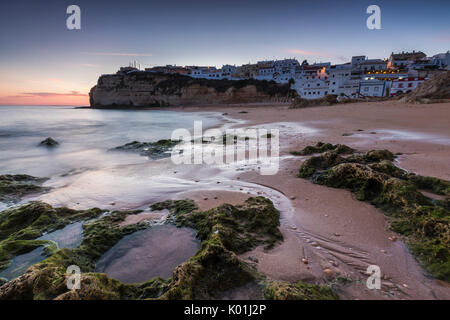 Sunset on the village perched on the promontory overlooking the beach of Carvoeiro Algarve Lagoa Faro District Portugal - Stock Photo