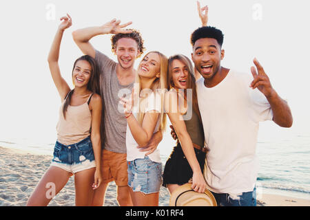 Group of happy friends having fun at ocean beach - Stock Photo