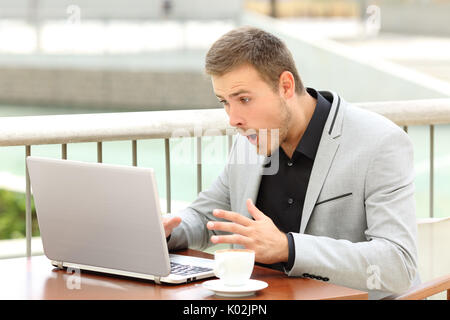 Amazed businessman receiving good news sitting in a coffee shop - Stock Photo