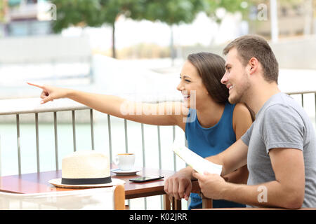 Couple ot tourists pointing locations sitting in a coffee shop - Stock Photo