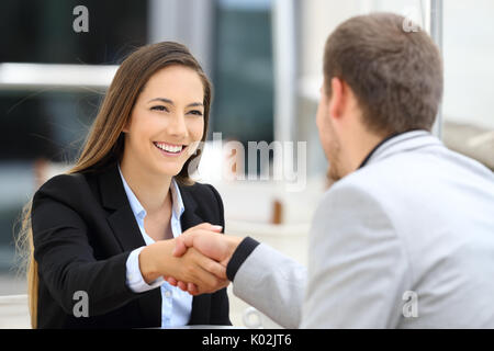 Two executives meeting and handshaking sitting in a coffee shop - Stock Photo