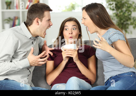 Upset friend in the middle of a couple argument at home - Stock Photo