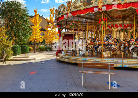 Bench in front of Merry-go-round with horses as trees with yellow leaves on background in autumn in Alba, Italy. - Stock Photo