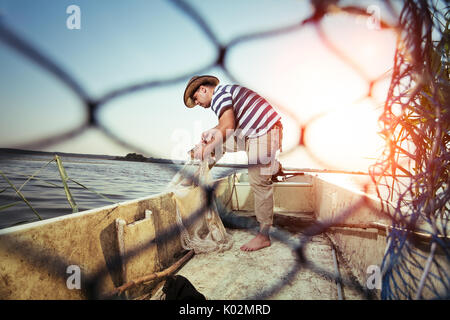 Fisherman fishing in the boat - Stock Photo