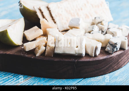 Cheese platter with blue cheese, soft cheese and aged cheese on rustic wooden board served with pear and crackers - Stock Photo