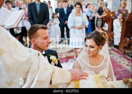 Intimate moment of a wedding couple making vows in the church during their wedding ceremony. - Stock Photo