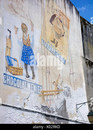 Historic advertising in Moissac, France - Stock Photo