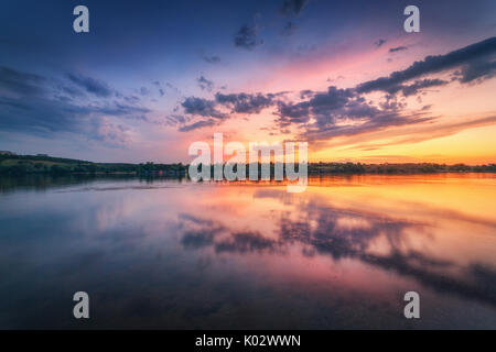 Beautiful scene with river and colorful sky with clouds at sunset. Amazing landscape with lake, blue sky with multicolored - Stock Photo