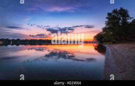 Tranquil scene with river and colorful sky with clouds at sunset. Amazing landscape with lake, blue sky with orange - Stock Photo