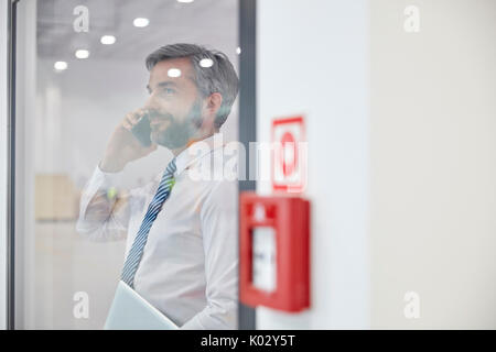 Male supervisor talking on cell phone at window in factory - Stock Photo