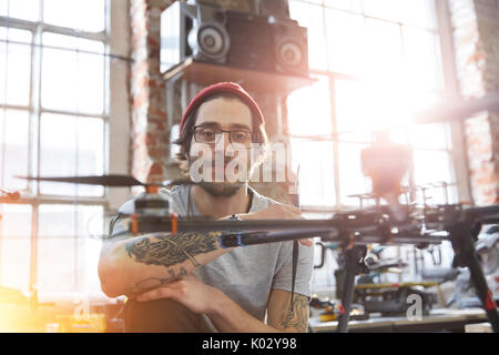 Portrait confident male designer with tattoos working on drone in workshop - Stock Photo