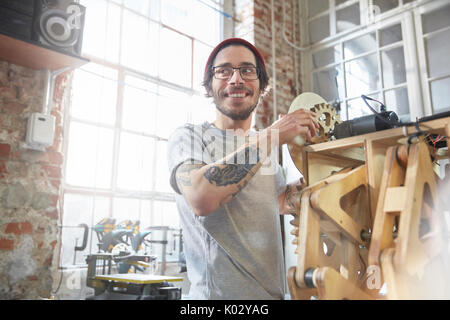 Male designer with tattoos working on prototype in workshop - Stock Photo
