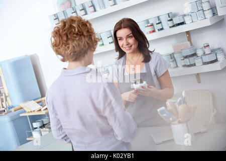 Female business owner using credit card reader, helping customer at counter in art paint shop - Stock Photo