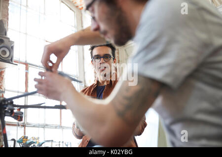 Male designers assembling drone in workshop - Stock Photo