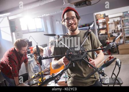 Portrait smiling male designer holding drone in workshop - Stock Photo