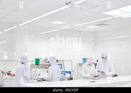 Engineers in clean suits using machinery in fiber optics research and testing lab - Stock Photo