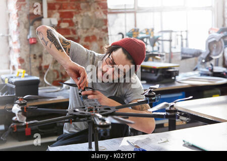 Male designer with tattoos assembling drone in workshop - Stock Photo