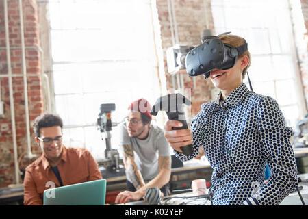 Female designer texting virtual reality simulator glasses and using joystick in workshop - Stock Photo