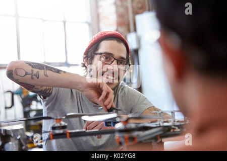 Smiling male designer with tattoos assembling drone - Stock Photo