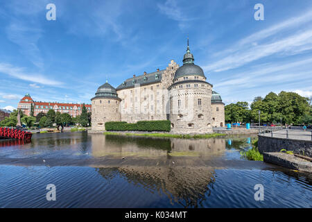 Orebro castle reflecting in water on sunny summer day in city Orebro, Sweden - Stock Photo