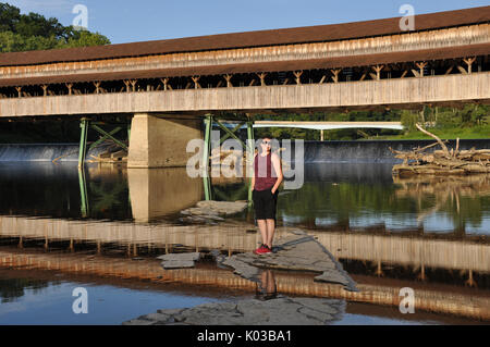 Woman Standing on Rock with Waterfalls and Covered Bridge in the Background at the Harpersfield Covered Bridge Metro - Stock Photo