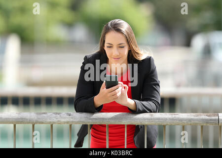 Front view portrait of a serious executive using a mobile phone outdoors - Stock Photo
