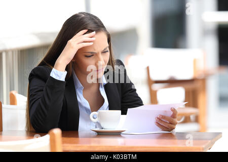 Worried executive reading a letter sitting in a coffee shop - Stock Photo