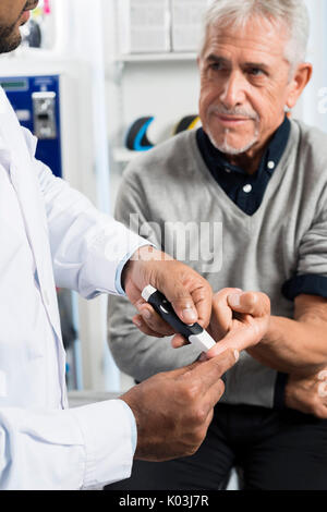 Doctor Checking Of Senior Patient's Sugar Level With Glucometer - Stock Photo
