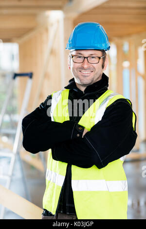 Mature Carpenter Standing Arms Crossed At Construction Site - Stock Photo