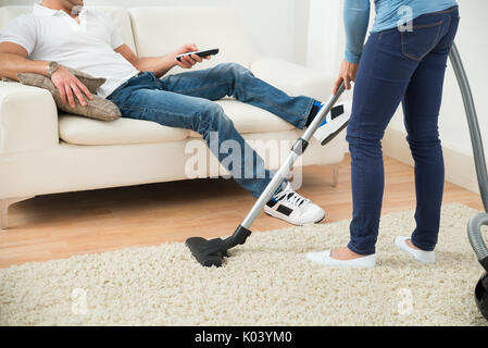 Close-up Of A Woman Cleaning Carpet In Front Of Man Sitting On Couch - Stock Photo