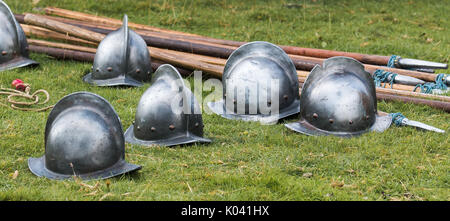 English Civil War reenactor's helmets sit on the grass. In the background are pikes. - Stock Photo