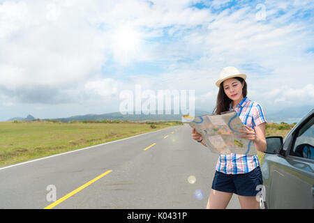 beautiful hat woman holding paper map finding right tourist route standing next to personal travel car with sunny - Stock Photo