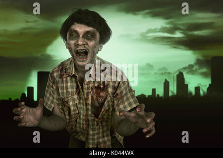 Horrible asian zombie man with wound in the body standing on the dark city - Stock Photo