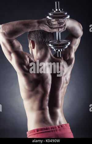 Strong athletic man with dumbbells behind his back on a dark background - Stock Photo