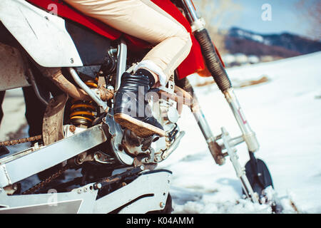 Feet on the bottom of the motorcycle in winter - Stock Photo