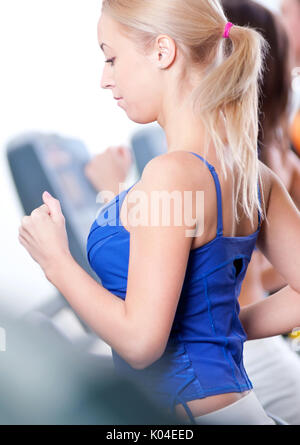 Two young women run on machine in the gym - Stock Photo
