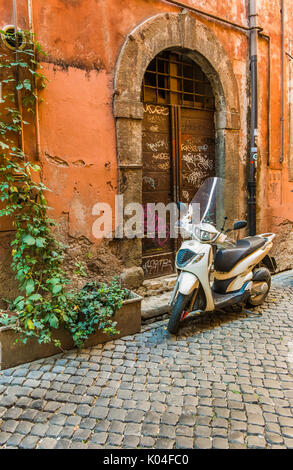scooter parked in front of a historic doorway - Stock Photo