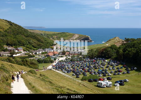 Lulworth Cove and masses of cars in the overflow carpark on a warm summer's weekend with tourists enjoying the sunshine, - Stock Photo