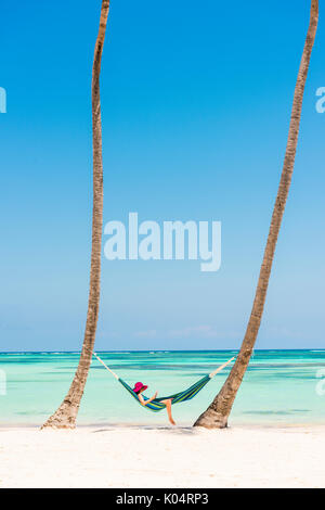 Juanillo Beach (playa Juanillo), Punta Cana, Dominican Republic. Woman relaxing on a hammock on a palm-fringed beach - Stock Photo