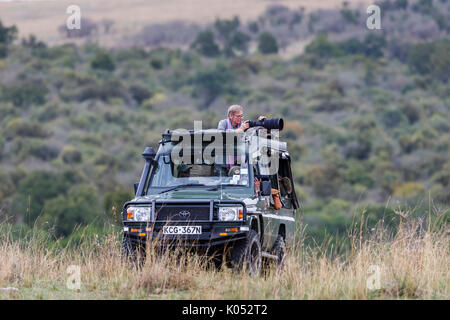 Safari tourists stand to train their long telephoto lenses on wildlife from a typical open jeep safari vehicle in - Stock Photo