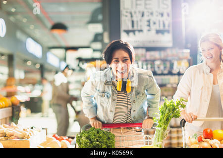 Portrait playful young woman with shopping cart grocery shopping in market - Stock Photo
