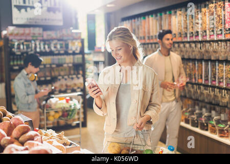 Young woman using cell phone, grocery shopping in market - Stock Photo